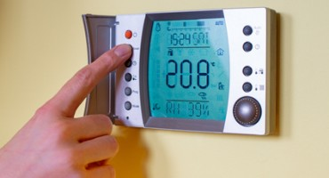 Closeup of a woman's hand setting the room temperature on a modern programmable thermostat. Save energy and money concept